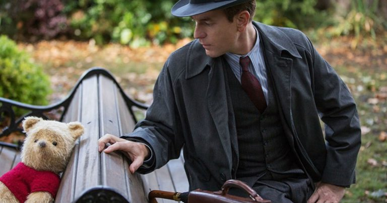 Winnie the Pooh and an adult Christopher Robin (Ewan McGregor) meet again on a park bench in Disney's Christopher Robin movie